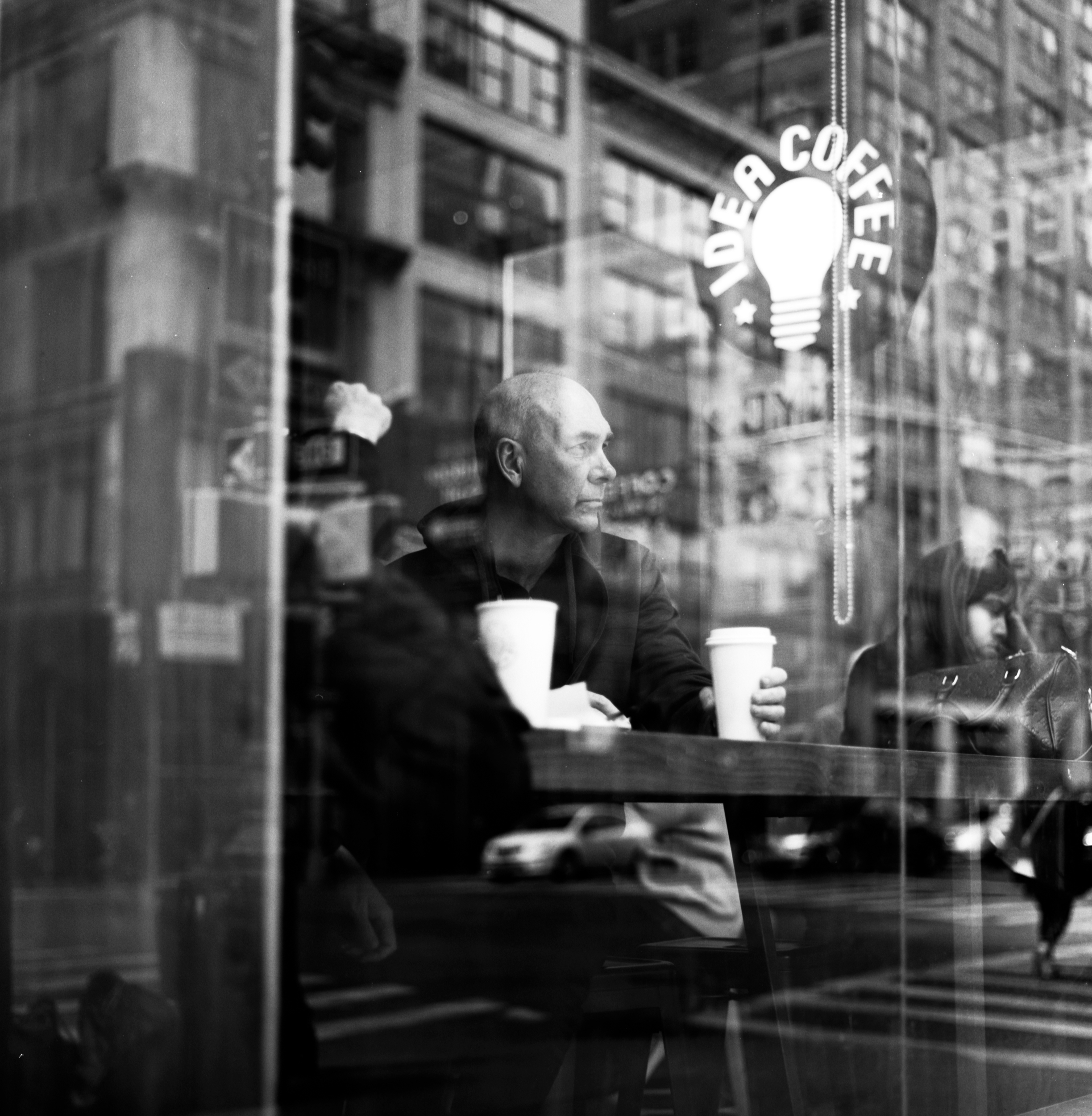 michelle viljoen, street photography, new york city, photography, new york city, 120mm film, hasselblad 500, man sitting in coffee shop in new york city, reflection photography