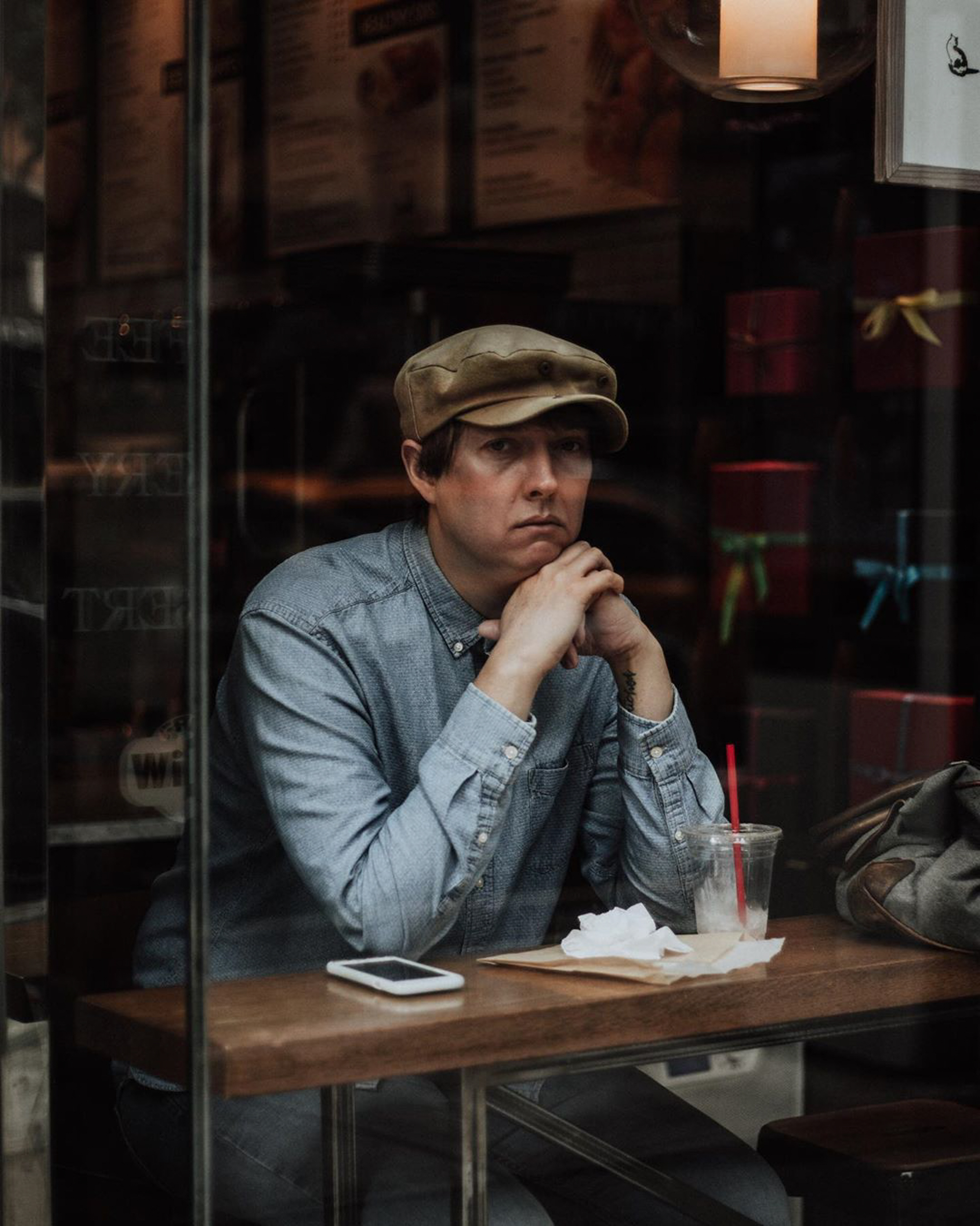woman sitting in a coffee shot, photography of a woman in the window, old man sitting in a diner, michelle viljoen, photography, street photography, new york, new york street photography, reflection photography,