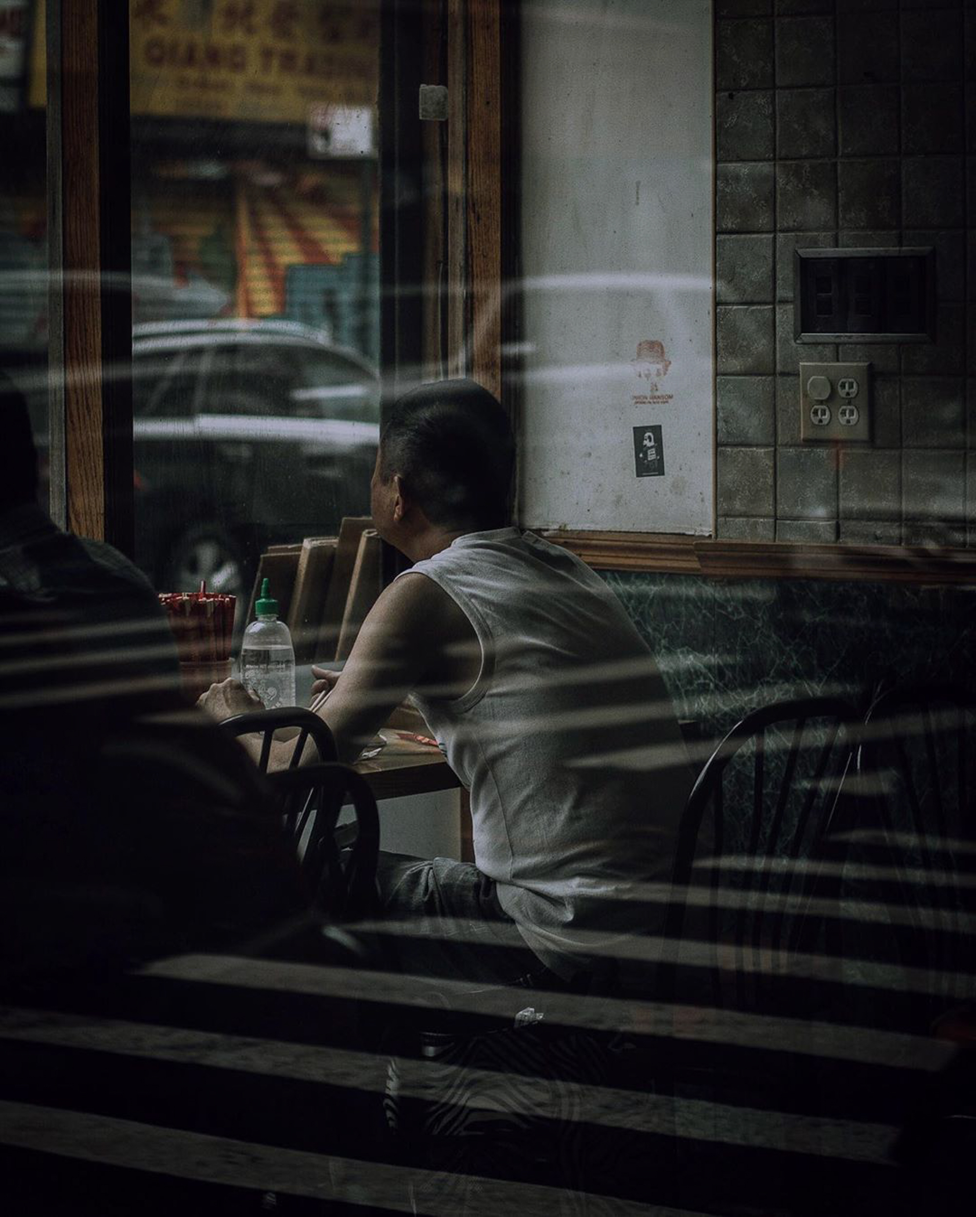 man sitting in a bar, street photography of a woman in the window, old man sitting in a diner, michelle viljoen, photography, street photography, new york, new york street photography, reflection photography,